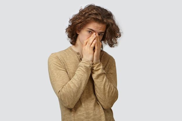 Portret atrakcyjnego, stylowego niezadowolonego młodego mężczyzny z obszernymi włosami zakrywającymi usta i nos obiema rękami, wstrzymując oddech z powodu nieprzyjemnego zapachu, patrząc, pozując na białym tle