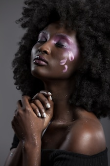 Portret atrakcyjnej african-american kobiety z pięknym makijażem, pozowanie z zamkniętymi oczami