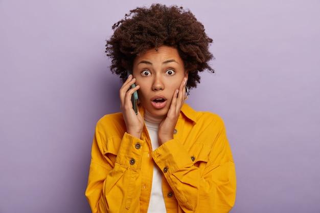 Portret atrakcyjnej afro dostaje zaskakującą wiadomość podczas rozmowy telefonicznej, dotyka policzka, nosi jasną, żelową kurtkę, ma wyskakujące oczy i otwarte usta, słyszy zdumiewające znaczenie stoi w pomieszczeniu