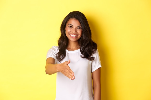 Portret atrakcyjnej afrykańskiej dziewczyny uśmiechającej się wyciągającej rękę na powitanie uścisku dłoni