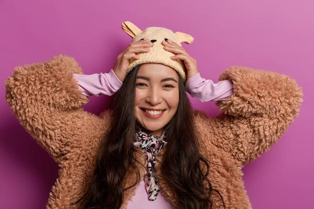 Portret atrakcyjnej azjatki chętnie kupuje nowy kapelusz, trzyma ręce na głowie, szczerze się uśmiecha, nosi zimowe ubrania, pokazuje białe zęby