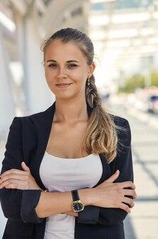 Portret atrakcyjnej bizneswoman stojącej przed oknami budynek biurowy