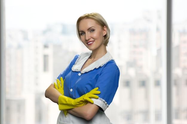 Portret atrakcyjnej blond sprzątaczki ze skrzyżowanymi rękami