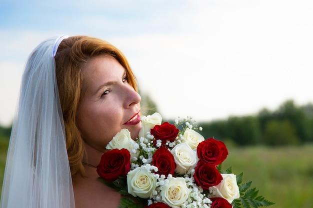 Portret atrakcyjnej brązowowłosej kobiety w welonie z pięknym uśmiechem i czerwoną szminką, z bukietem czerwonych i białych róż na wiejskim polu, bukiet panny młodej