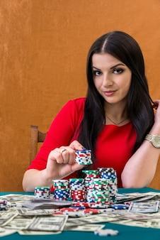 Portret atrakcyjnej brunetki kobiety z żetonami w kasynie