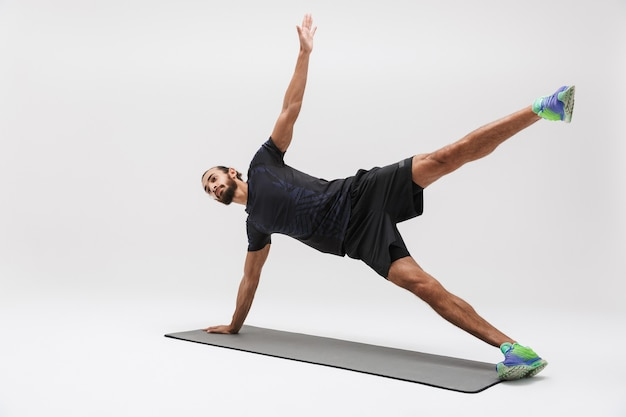 Portret atrakcyjnej brunetki sportowca w dresie robi trening na macie do jogi na białym tle