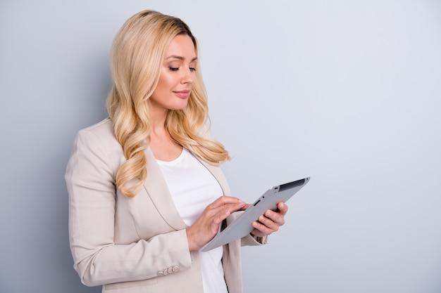 Portret atrakcyjnej, czarującej, skoncentrowanej, wykwalifikowanej kobiety trzymającej za pomocą tabletu