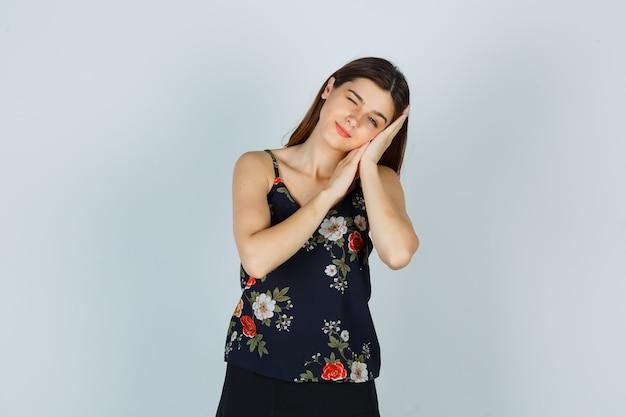 Portret atrakcyjnej damy opartej na dłoniach jako poduszce w bluzce i patrzącej na senny widok z przodu