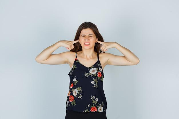 Portret atrakcyjnej damy zatykającej uszy palcami w bluzce i patrzącej na przestraszony widok z przodu