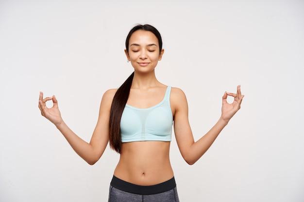 Portret atrakcyjnej, dorosłej azjatyckiej dziewczyny o ciemnych długich włosach zebranych w kucyk. ubrana w strój sportowy i medytująca, ma zamknięte oczy, relaksując się. stojak na białym tle na białym tle