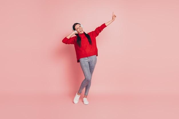 Portret atrakcyjnej dziewczęcej dziewczyny słuchającej przeboju odizolowanej na różowym tle