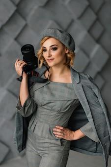 Portret atrakcyjnej dziewczyny fotografa w stylowych ubraniach i berecie z aparatem w dłoniach. pojęcie zawodów kreatywnych.