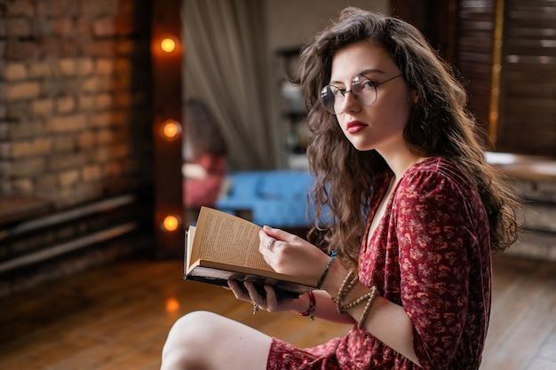 Portret atrakcyjnej dziewczyny studentów z kręconymi włosami, w krótkiej czerwonej sukience i okrągłych okularach. młoda kobieta patrzeje w kamerze podczas gdy siedzący w loft mieszkaniu i czytelniczej książce w ona ręki.