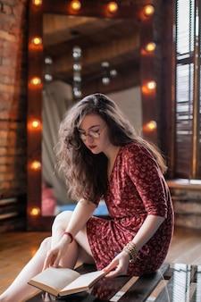 Portret atrakcyjnej dziewczyny studentów z kręconymi włosami, w krótkiej czerwonej sukience i okrągłych okularach. młodej kobiety obsiadanie na szklanym stolik do kawy w loft mieszkaniu i czytelnicza książka w ona ręki.