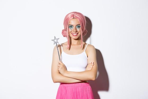 Portret atrakcyjnej dziewczyny z różową peruką i jasnym makijażem, patrząc pewnie w swój strój wróżki, trzymając różdżkę i uśmiechając się.