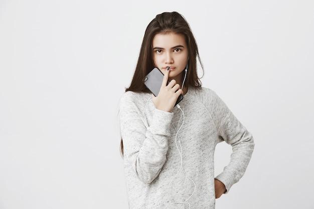 Portret atrakcyjnej europejskiej kobiety trzymającej w ręku telefon, dotykającej ust palcem wskazującym, wyrażający ciekawość i chęć poznania odpowiedzi.