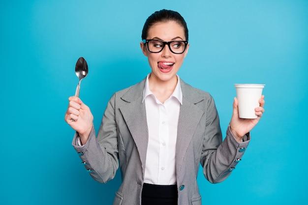 Portret atrakcyjnej głodnej wesołej zabawnej pani jedzącej smaczny, pyszny lunch jogurt lizanie warg na białym tle na jasnym niebieskim tle koloru