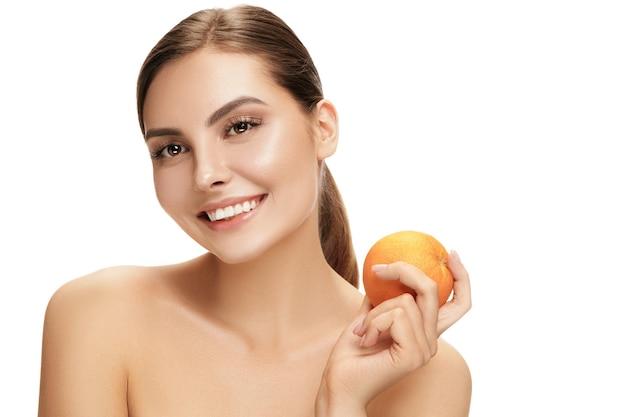 Portret atrakcyjnej kaukaskiej kobiety uśmiechający się na białym tle na białej ścianie z pomarańczowymi owocami. uroda, pielęgnacja, skóra, leczenie, zdrowie, spa, kosmetyki