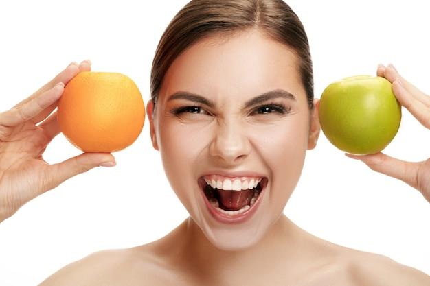 Portret atrakcyjnej kaukaskiej uśmiechniętej kobiety na białym tle studio z zielonym jabłkiem i pomarańczowymi owocami