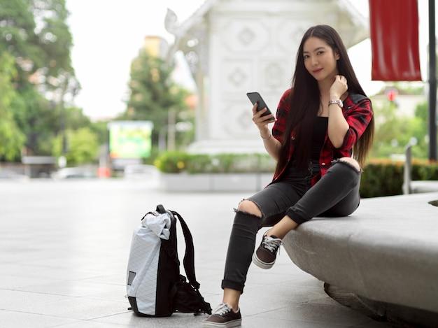 Portret atrakcyjnej kobiecej turystki pozującej ze smartfonem w dłoni i plecakiem na ulicy miasta