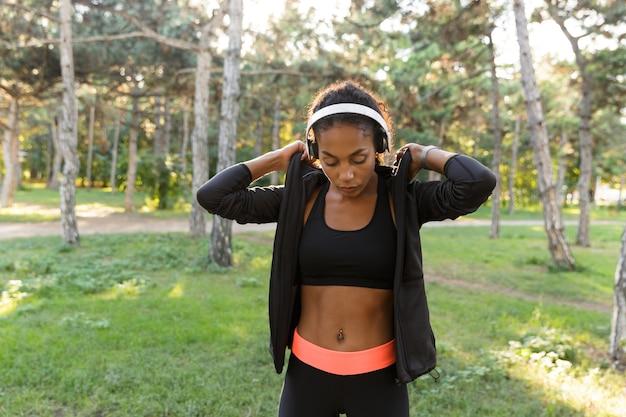 Portret atrakcyjnej kobiety 20s na sobie czarny dres i słuchawki, spacerując po zielonym parku