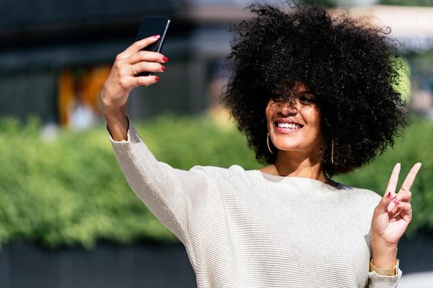 Portret atrakcyjnej kobiety afro biorącej portret selfie na ulicy