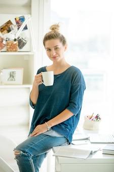 Portret atrakcyjnej kobiety siedzącej przy stole