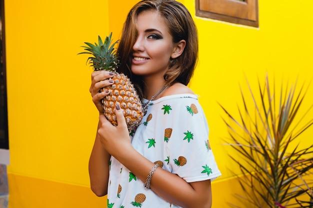 Portret atrakcyjnej kobiety w pintowanej koszulce na letnich wakacjach trzymającej ananasa, detoksykacja diety owocowej, opalona skóra, jasne żółte tło