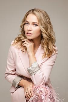 Portret atrakcyjnej kobiety w różowej sukience z blond włosami pozuje do aparatu z otwartymi ustami
