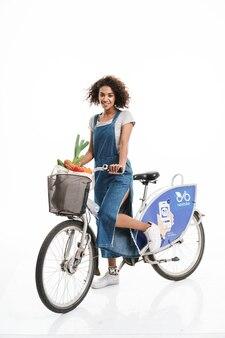 Portret atrakcyjnej kobiety z torbą na zakupy uśmiecha się podczas jazdy na rowerze na białym tle nad białą ścianą