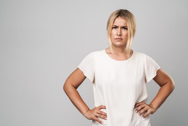 Portret atrakcyjnej, marszczącej brwi, zdezorientowanej kobiety stojącej na białym tle nad szarą ścianą