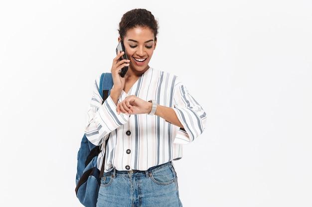 Portret atrakcyjnej młodej afrykańskiej kobiety niosącej plecak stojący na białym tle nad białą ścianą, rozmawiającej przez telefon komórkowy