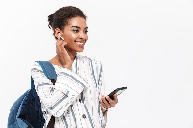 Portret atrakcyjnej młodej afrykańskiej kobiety niosącej plecak stojący na białym tle nad białą ścianą, słuchający muzyki za pomocą bezprzewodowych słuchawek, trzymający telefon komórkowy