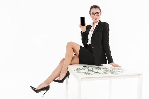Portret atrakcyjnej młodej bizneswoman w wizytowym stroju, siedzącej na biurku na białym tle nad białą ścianą, pokazującej pusty ekran telefonu komórkowego