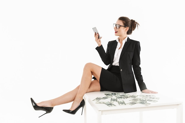 Portret atrakcyjnej młodej bizneswoman w wizytowym stroju, siedzącej na biurku na białym tle nad białą ścianą, rozmawiającej przez telefon komórkowy