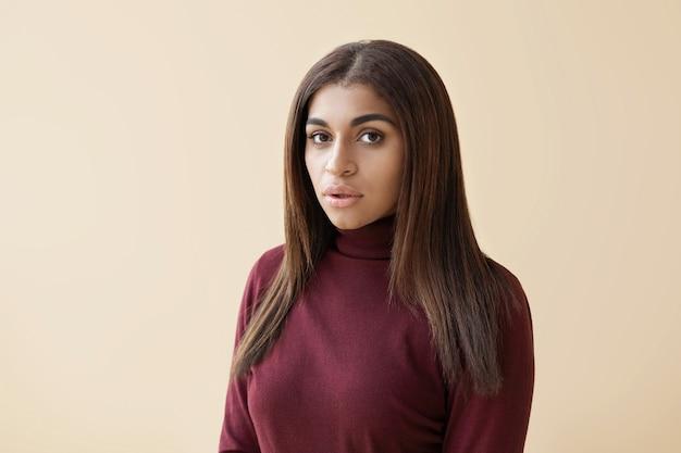 Portret atrakcyjnej młodej damy rasy mieszanej z długimi włosami, ubrana w bordowy sweter z golfem stojący
