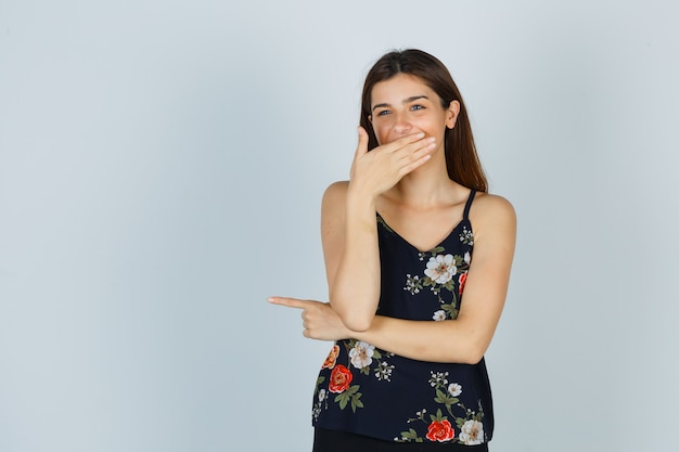 Portret atrakcyjnej młodej damy trzymającej rękę na ustach, uśmiechającej się w bluzce i patrzącej na wesoły widok z przodu