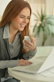 Portret atrakcyjnej młodej kobiety komunikującej się za pośrednictwem laptopa