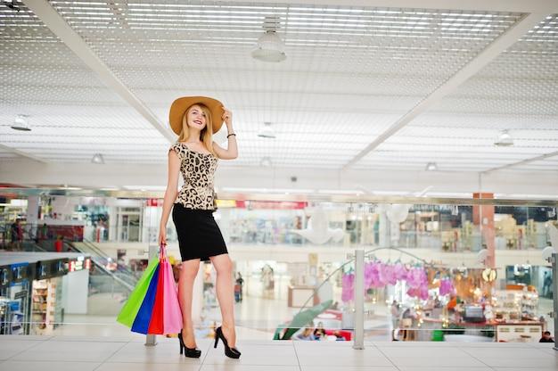 Portret atrakcyjnej młodej kobiety w bluzie lamparta, czarnej spódnicy z czapką i torbach na zakupy.