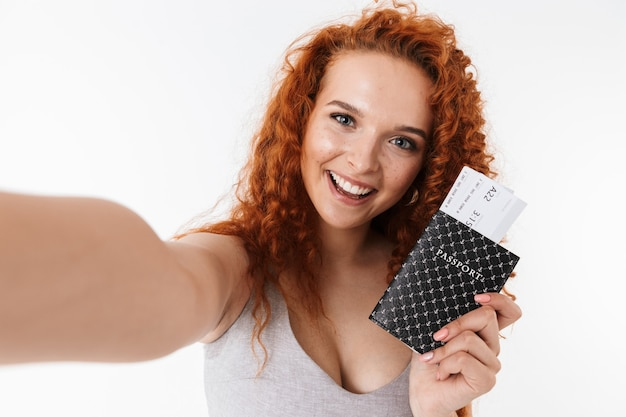 Portret atrakcyjnej młodej kobiety z długimi kręconymi rudymi włosami stojącej na białym tle, robiącej selfie, pokazując paszport z biletami lotniczymi