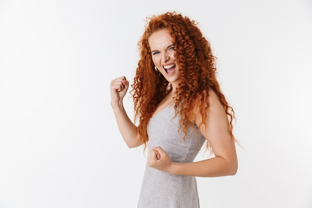 Portret atrakcyjnej młodej kobiety z długimi kręconymi rudymi włosami stojącej na białym tle, świętującej sukces