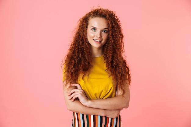 Portret atrakcyjnej młodej kobiety z długimi kręconymi rudymi włosami stojącej na białym tle, z założonymi rękami
