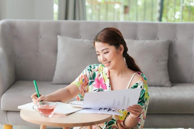 Portret atrakcyjnej młodej studentki odrabiającej pracę domową w domu
