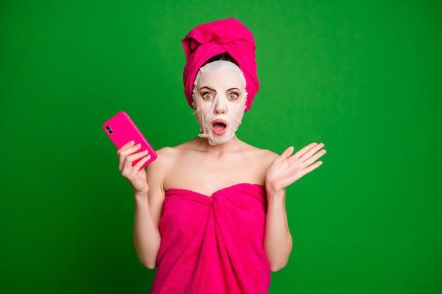 Portret atrakcyjnej nagiej zdumionej kobiety noszącej turbanową maskę na twarz, używającej reakcji na wiadomości gadżetowe odizolowanej na jasnozielonym tle