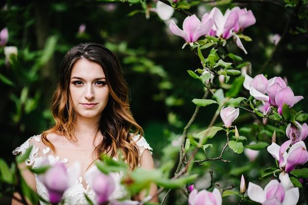 Portret atrakcyjnej narzeczonej na tle różowych kwiatów magnolii i zieleni.