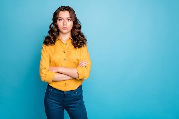 Portret atrakcyjnej pani biznesu kręcone trzymać ręce skrzyżowane poważnie wyglądający koledzy nie lubią przychodzących do pracy późno nosić żółte spodnie koszuli.