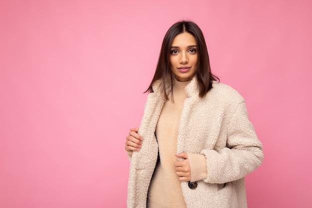 Portret atrakcyjnej pewnej siebie pozytywnej, dobrze wyglądającej stylowej młodej brunetki na sobie jesień beżowy ciepły płaszcz na białym tle na różowym tle z wolnej przestrzeni. koncepcja mody.