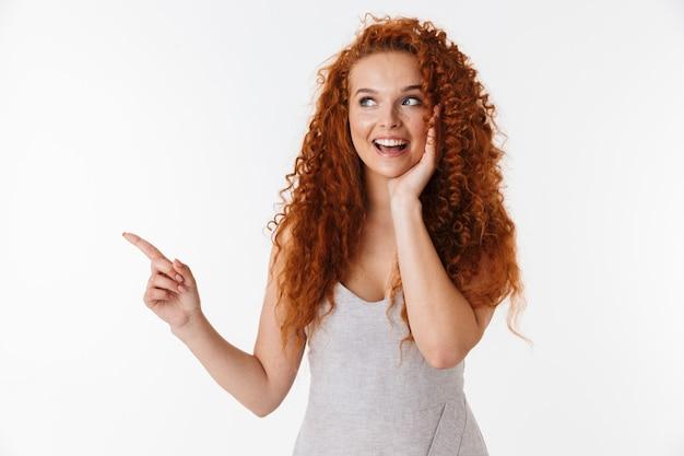 Portret atrakcyjnej podekscytowanej młodej kobiety z długimi kręconymi rudymi włosami stojącej na białym tle, przedstawiającej miejsce na kopię, wskazującej