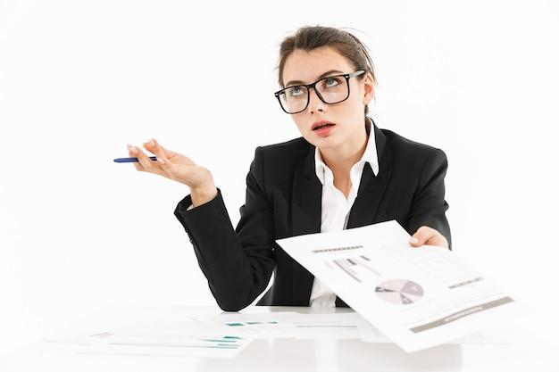 Portret atrakcyjnej, pracowitej młodej bizneswoman w wizytowym stroju, siedzącej przy biurku odizolowanej nad białą ścianą, pracującej nad projektem