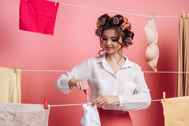 Portret atrakcyjnej, pracowitej, wesołej gospodyni domowej wieszającej mokre ubrania na sznurku, odizolowane na różowej ścianie